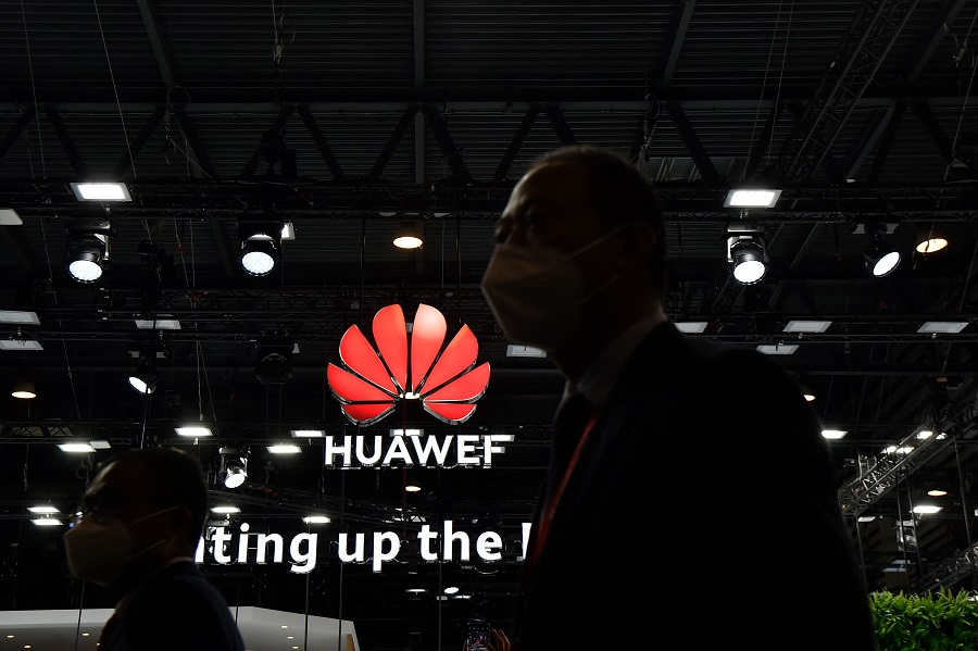 Visitors walk by the Huawei stand at the Mobile World Congress (MWC) fair in Barcelona on 28 June 2021. (Pau Barrena/AFP)