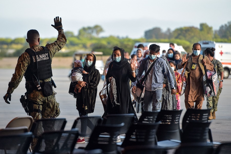 Refugees receive instructions from a US navy soldier as they disembark from a US air force aircraft after an evacuation flight from Kabul at the Rota naval base in Rota, Spain, on 31 August 2021. (Cristina Quicler/AFP)
