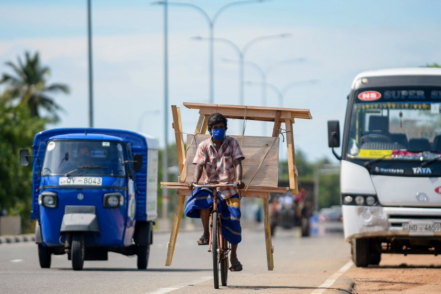 A man wearing a face mask transports wooden furniture on his bicycle along a street on the outskirts of Colombo, Sri Lanka, on 13 November 2020. (Lakruwan Wanniarachchi/AFP)