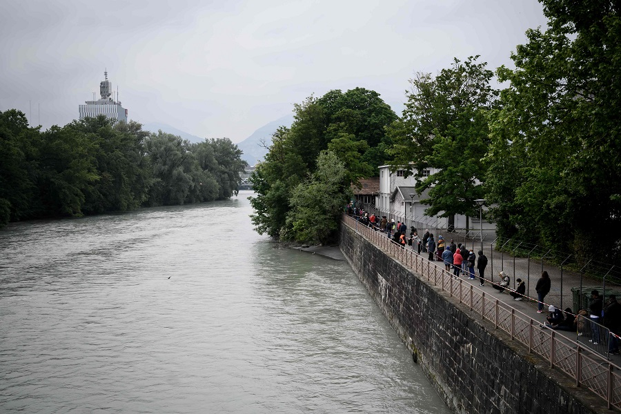 People in need queue along Arve river at a free food distribution center in Geneva on 16 May 2020. (Fabrice Coffrini/AFP)