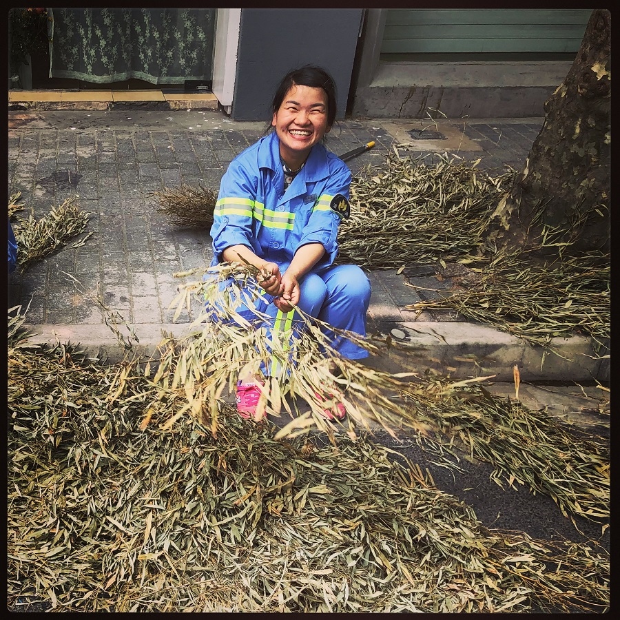 A street sweeper with a disarming smile takes a break from cleaning the streets of Huangpu, Shanghai to fix her straw broom.