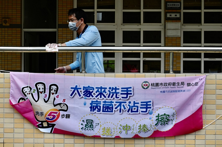 A man wearing a face mask cleans a handrail behind a sign telling students how to wash their hands amid the Covid-19 pandemic at a middle school in Taoyuan, Taiwan, on 29 February 2020. (Sam Yeh/AFP)