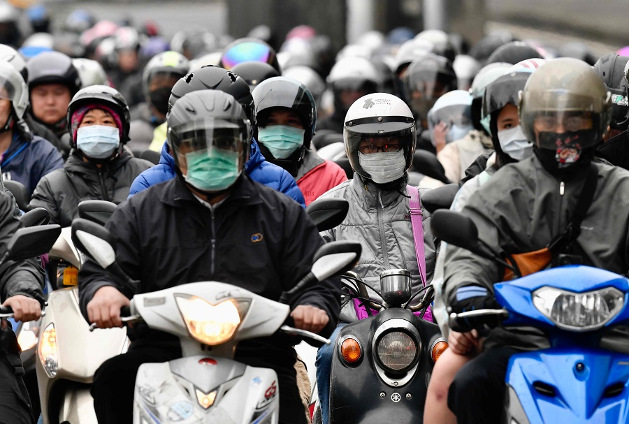 Motorcyclists wearing face masks amid the Covid-19 pandemic ride during the peak hours while heading to work in Taipei on 18 March 2020. (Sam Yeh/AFP)