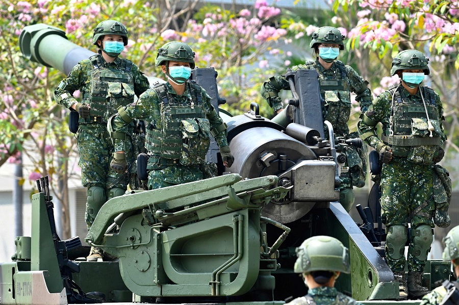 Female soldiers wearing face masks amid the Covid-19 pandemic stand in formation on a US-made M110A2 self-propelled howitzer during Taiwan President Tsai Ing-wen's visit to a military base in Tainan, Taiwan, on 9 April 2020. (Sam Yeh/AFP)