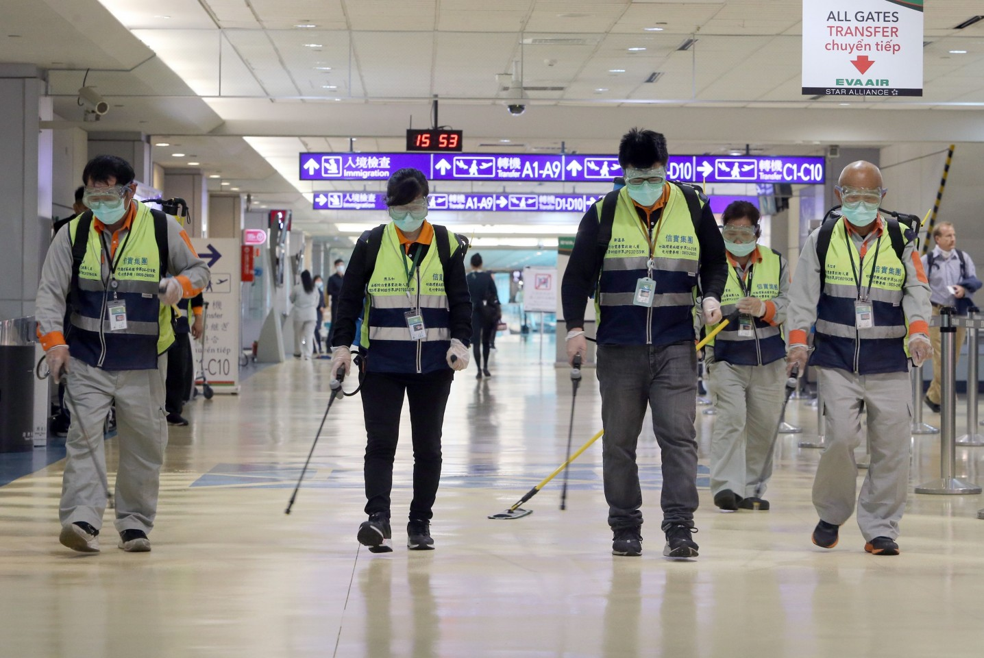 Masked workers disinfect a passenger throughfare at the Taoyuan International Airport on 22 January 2020, after Taiwan reported its first case of the new SARS-like virus from China on 21 Jan. (Chen Chi-chuan/AFP)