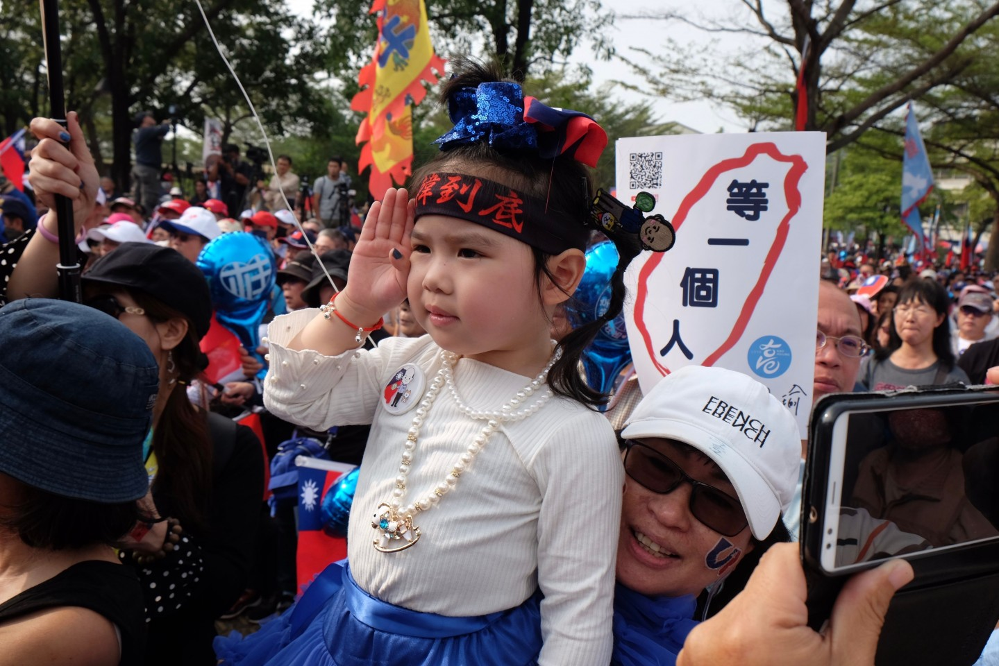 A little girl salutes during a campaign rally for Han Kuo-Yu, KMT's presidential candidate, in Tainan on January 4, 2020. (Sam Yeh/AFP)
