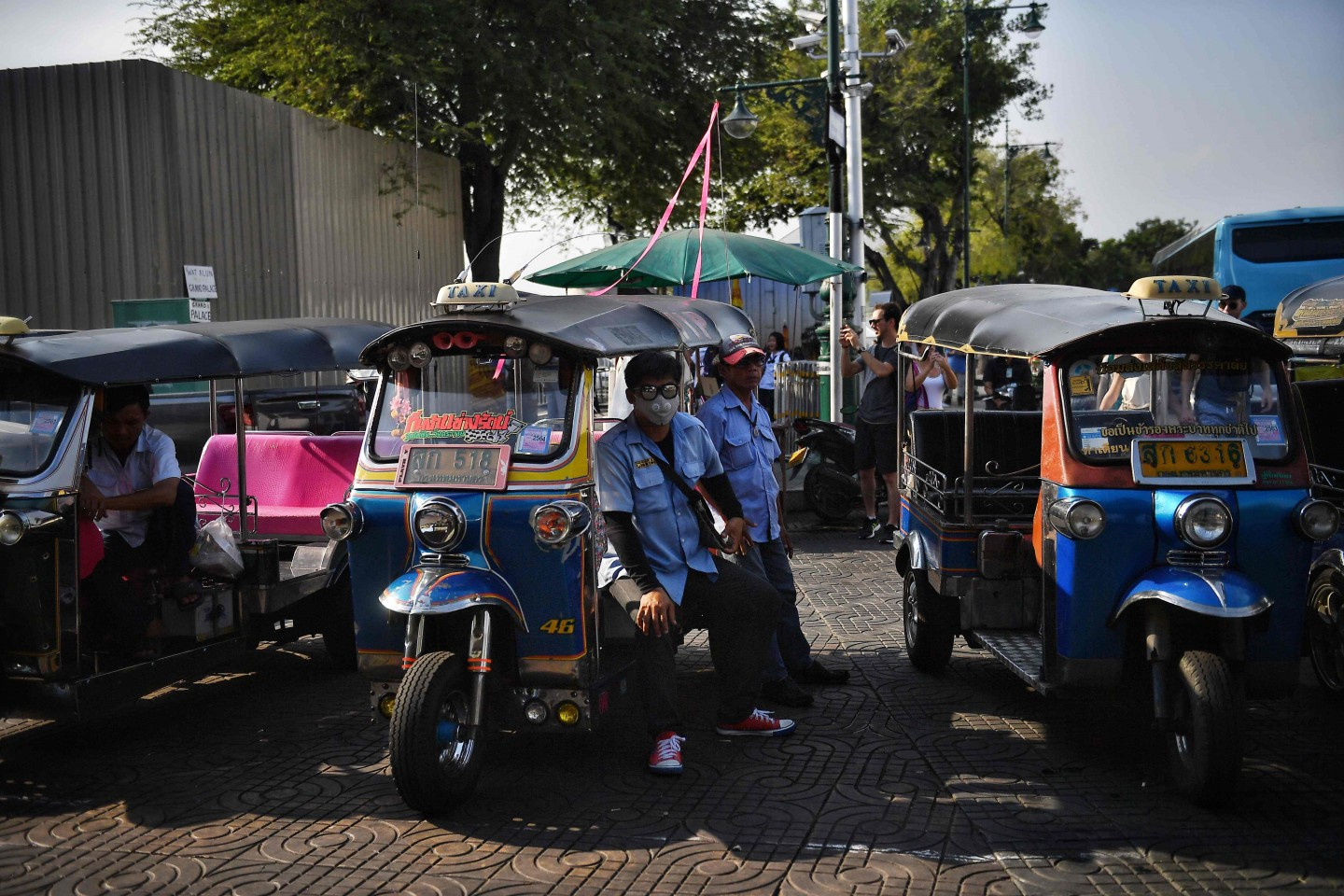 A tuk tuk driver in a protective facemask, amid fears over the spread of the COVID-19 coronavirus, waits for customers near the Grand Palace in Bangkok on 17 February 2020. (Lillian Suwanrumpha/AFP)
