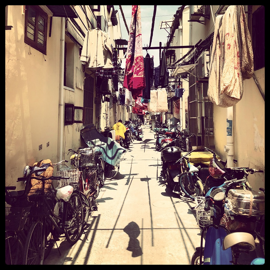 Parked bicylces and laundry share a lane on a sunny day in Huangpu district.