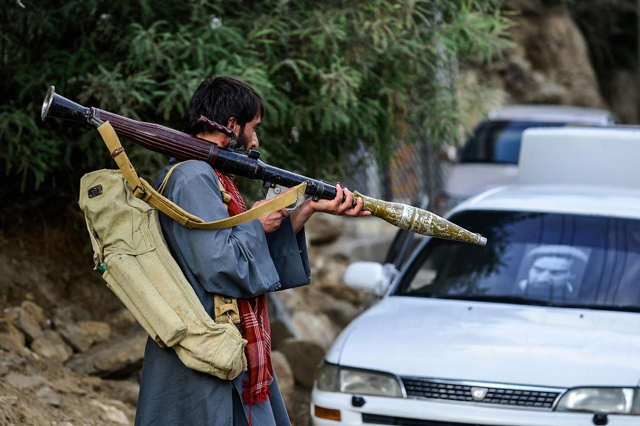 An Afghan armed man supporting the Afghan security forces against the Taliban carries a weapon as he walks along a road in Bazarak, Panjshir province, Afghanistan, on 18 August 2021. (Ahmad Sahel Arman/AFP)