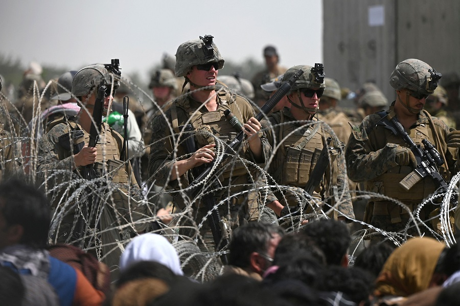US soldiers stand guard behind barbed wire as Afghans sit on a roadside near the military part of the airport in Kabul, Afghanistan, on 20 August 2021, hoping to flee from the country after the Taliban's military takeover of Afghanistan. (Wakil Kohsar/AFP)