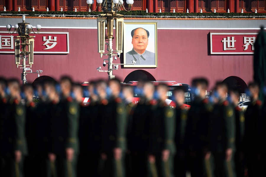 The portrait of late communist leader Mao Zedong is seen behind paramilitary police officers as they gather in Beijing's Tiananmen Square on 23 October 2020. (Noel Celis/AFP)