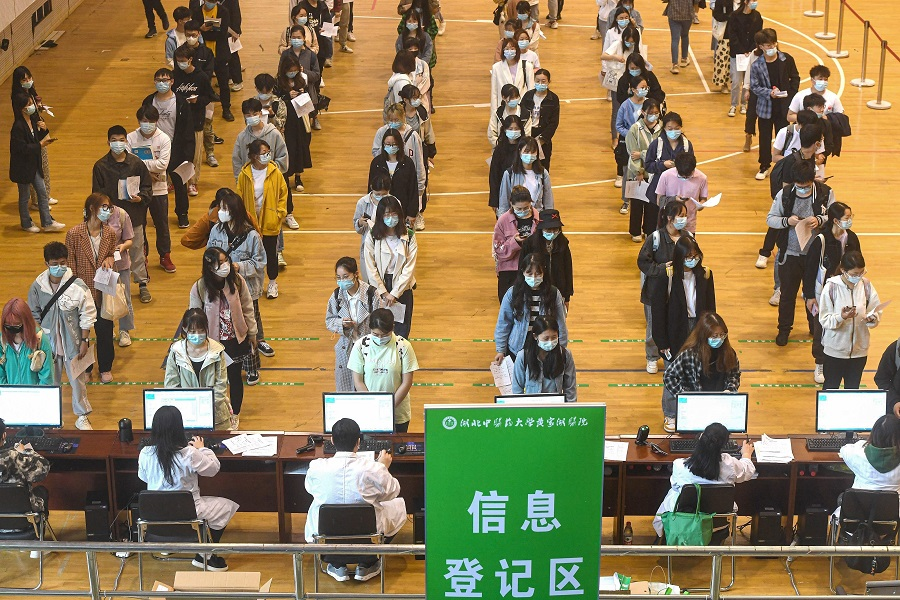 This photo taken on 27 April 2021 shows university students queueing to receive the China National Biotec Group (CNBG) Covid-19 coronavirus vaccine at a university in Wuhan, Hubei province, China. (STR/AFP)