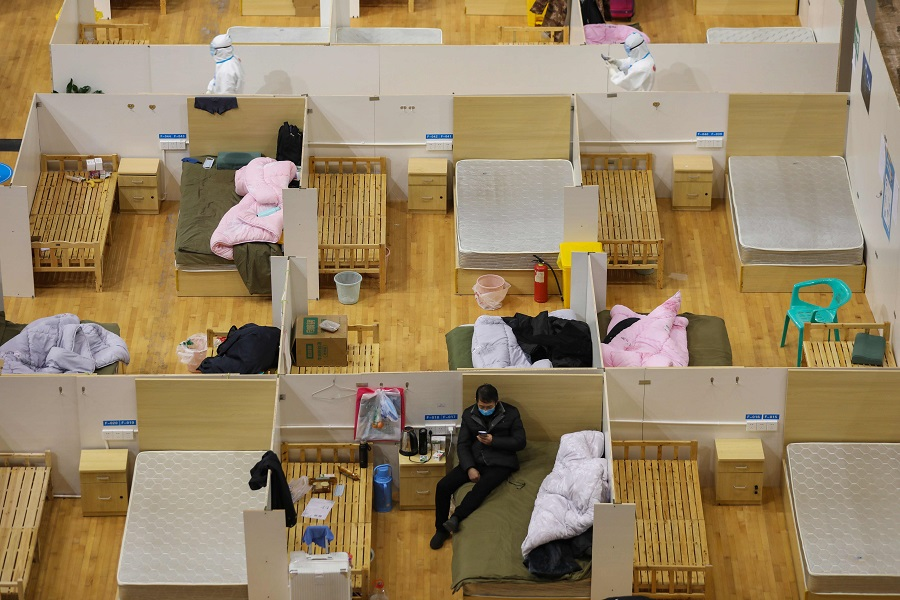 This photo taken on 5 March 2020 shows a medical worker (top left) walking past empty beds as a patient rests at a temporary hospital set up for Covid-19 coronavirus patients in a sports stadium in Wuhan. (STR/AFP)