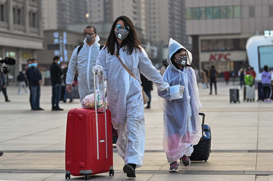 People wearing protective clothing and masks arrive at Hankou Railway Station in Wuhan, to board one of the first trains leaving the city in China's Hubei province early on 8 April 2020, after a ban on outward travel was lifted. (Hector Retamal/AFP)