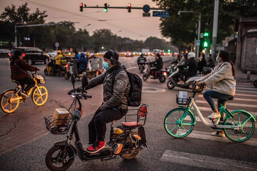 People wearing face masks commute during rush hour in Beijing on 15 October 2020. (Nicolas Asfouri/AFP)