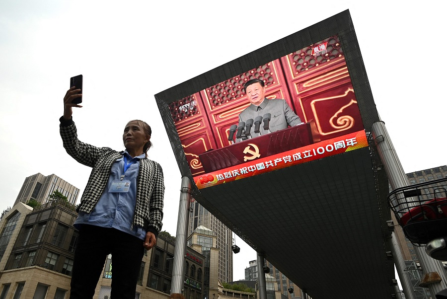 A woman takes a selfie as Chinese President Xi Jinping's speech is being broadcasted on a large screen in Beijing, China, during the 100th anniversary of the founding of the Communist Party of China on 1 July 2021. (Noel Celis/AFP)