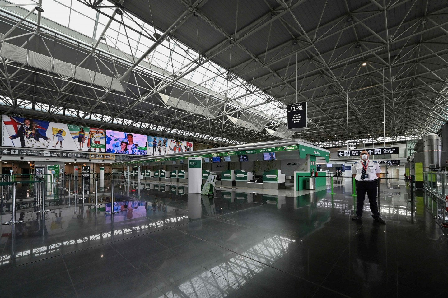 An airport security agent stands guard in a deserted Terminal T1 of Rome's Fiumicino international airport on 17 March 2020. (Andreas Solaro/AFP)