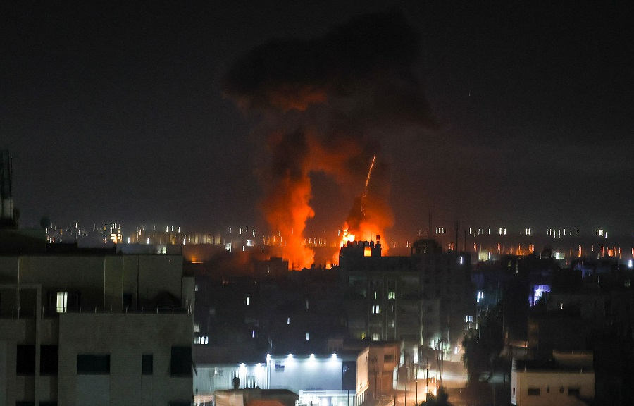 Explosions light up the night sky above buildings in Gaza City as Israeli forces shell the Palestinian enclave, early on 16 June 2021. (Mahmud Hams/AFP)