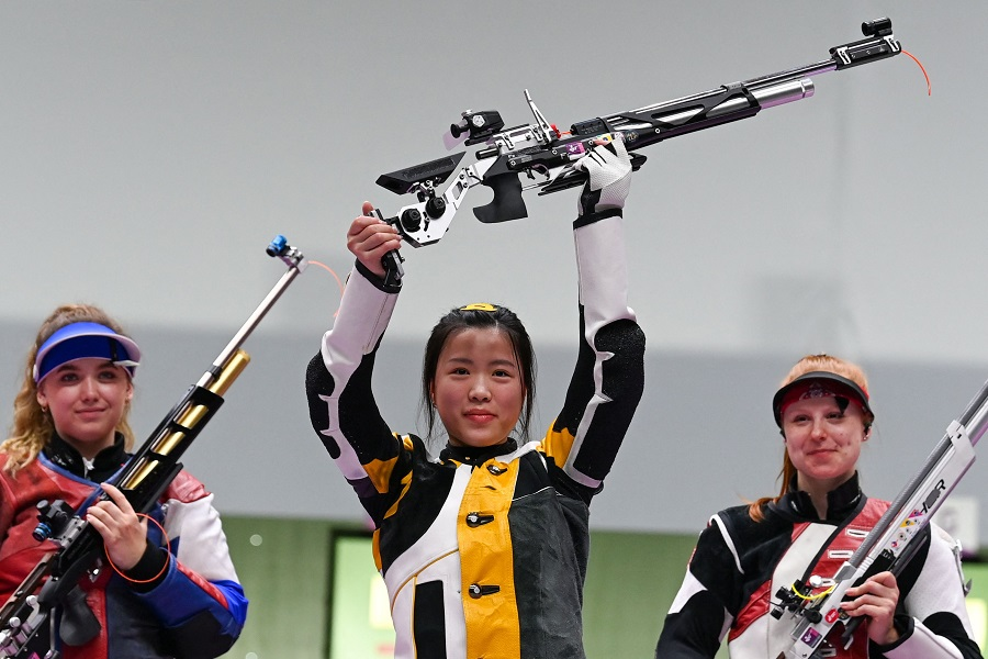 China's Yang Qian celebrates on the podium between Russia's Anastasiia Galashina (left) and Switzerland's Nina Christen after winning the women's 10m air rifle final during the Tokyo 2020 Olympic Games at the Asaka Shooting Range in the Nerima district of Tokyo on 24 July 2021. (Tauseef Mustafa/AFP)