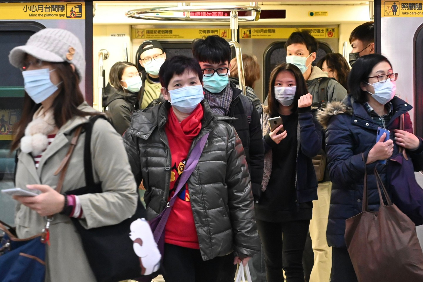 Mask-clad commuters get off a train at a train station in Taipei following the Lunar New Year holidays on 30 January 2020. (Sam Yeh/AFP)