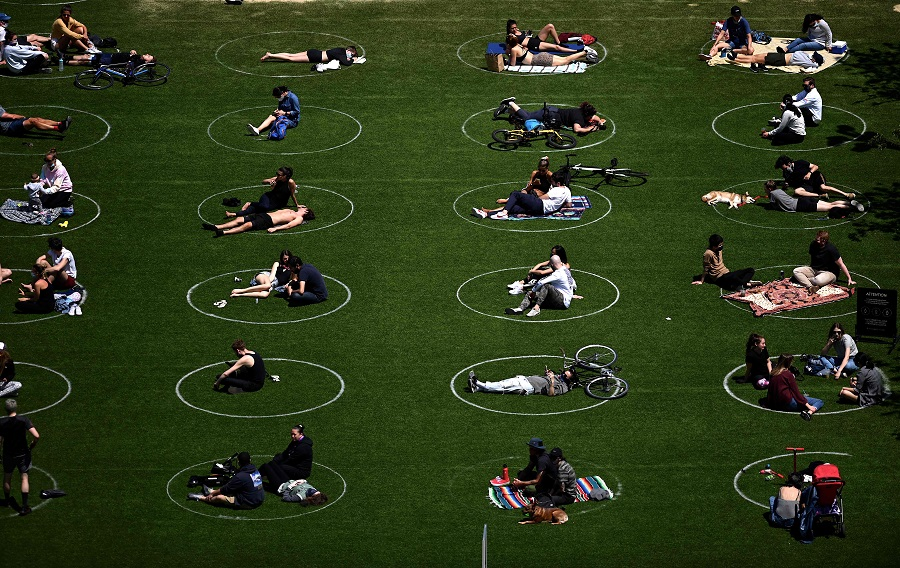 People are seen practising social distancing in white circles in Domino Park, during the Covid-19 pandemic on 17 May 2020, in the Brooklyn borough of New York City. (Johannes Eisele/AFP)