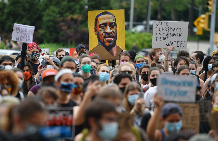"A protester holds up a portrait of George Floyd during a ""Black Lives Matter"" demonstration in front on 5 June 2020 in Brooklyn, New York. (Angela Weiss/AFP)"