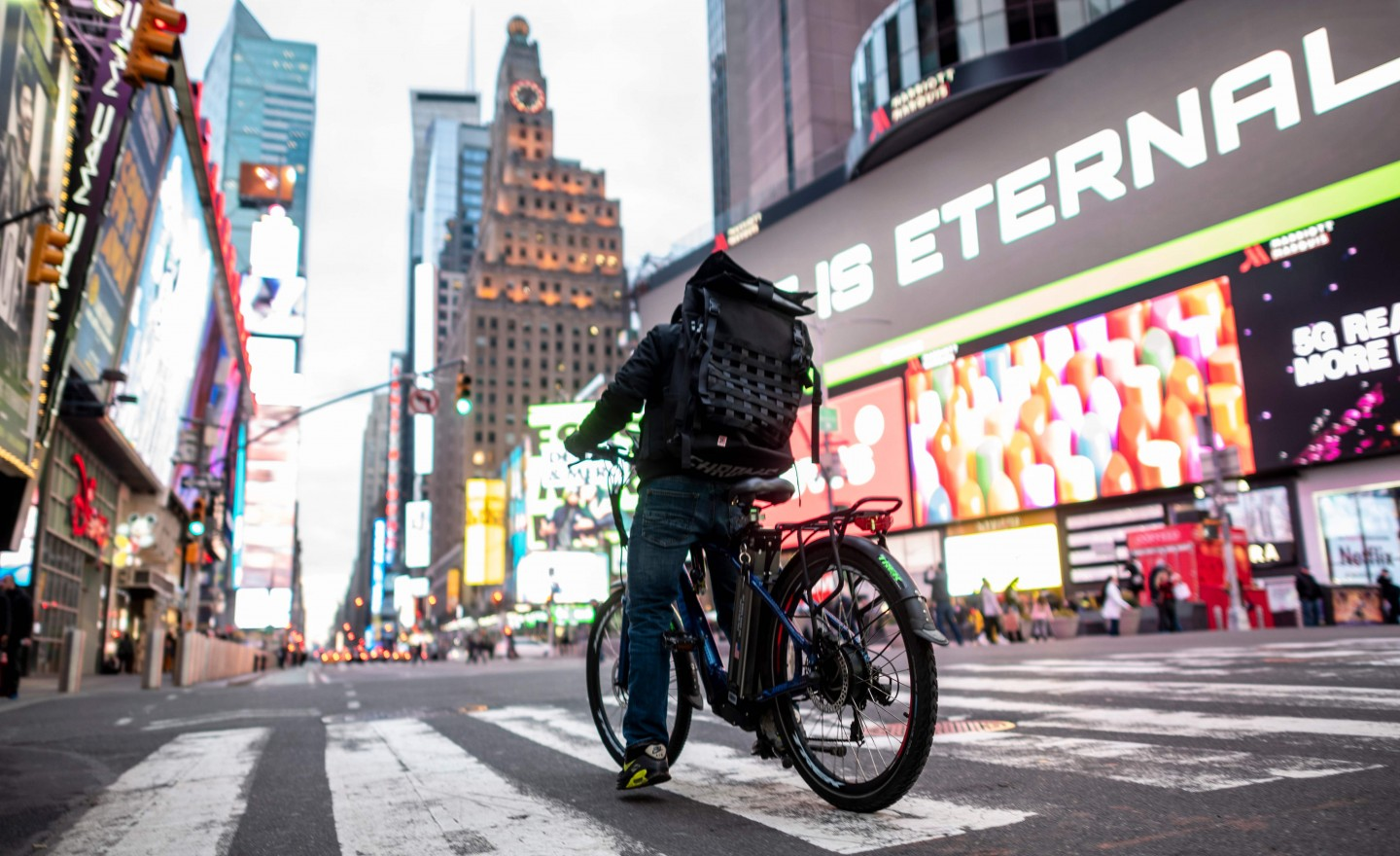 A food delivery man crosses the street in Times Square in Manhattan on 17 March 2020 in New York City. The coronavirus outbreak has transformed the US virtually overnight from a place of boundless consumerism to one suddenly constrained by nesting and social distancing. (Johannes Eisele/AFP)