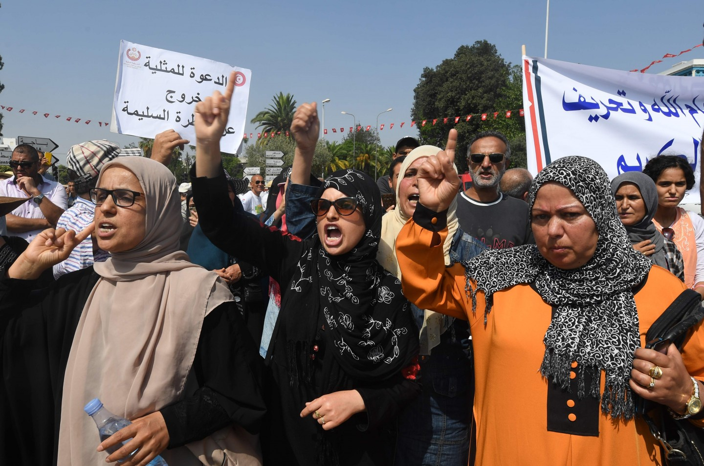 A commission set up by Tunisian President Beji Caid Essebsi to bring the legal code in line with the 2014 constitution adopted after the Arab Spring uprising, unveiled in June a raft of proposed liberal reforms. The photo shows hundreds of Tunisians holding pro-conservative signs during a protest against proposed reforms opposed by conservative Muslims that include equal inheritance rights for women and decriminalising homosexuality, on August 11, 2018 in Tunis. (Photo by Fethi Belaid/AFP)