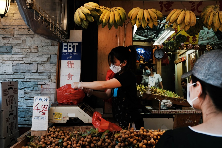 A vendor wearing a protective face mask works in New York City's Chinatown on 10 August 2020 in New York City. (Spencer Platt/Getty Images/AFP)