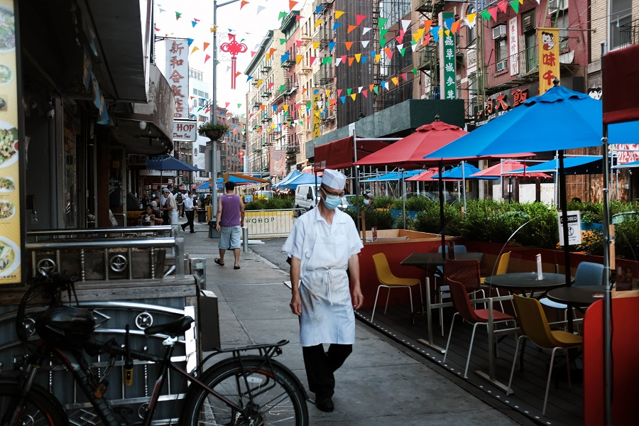 A worker walks past an outdoor dining area in New York City's Chinatown on 10 August 2020 in New York City. (Spencer Platt/Getty Images/AFP)