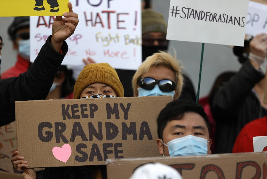 People hold signs during a rally in solidarity with Asian hate crime victims outside of the San Francisco Hall of Justice on 22 March 2021 in San Francisco, California, US. (Justin Sullivan/Getty Images/AFP)