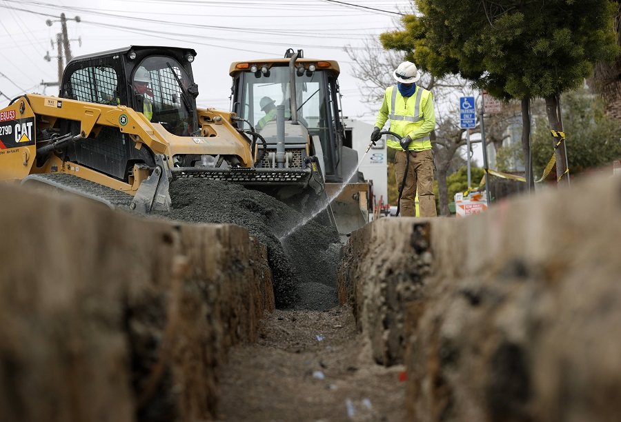 Workers with East Bay Municipal Utility District (EBMUD) fill a trench after installing new water pipe on 22 April 2021 in Oakland, California, US. (Justin Sullivan/Getty Images/AFP)