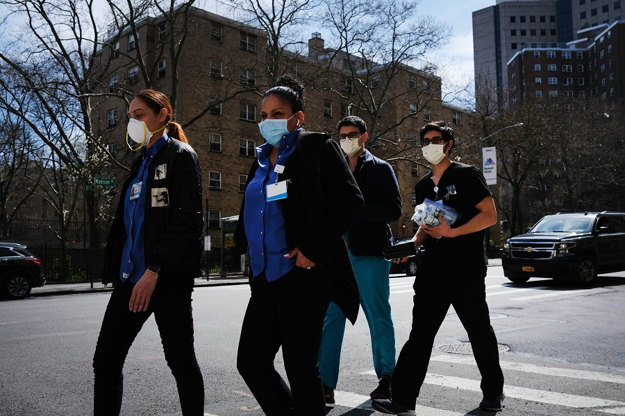 Medical workers walk outside of Mount Sinai Hospital amid the coronavirus pandemic on 01 April 2020 in New York City. (Spencer Platt/Getty Images/AFP)