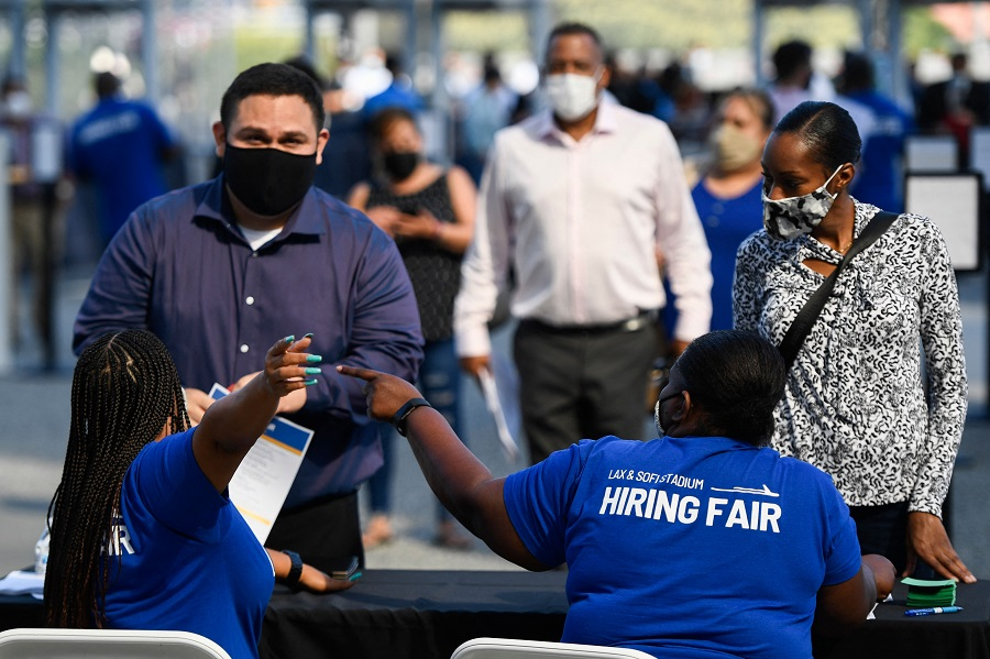 People receive information as they attend a job fair for employment with SoFi Stadium and Los Angeles International Airport employers, at SoFi Stadium on September 9, 2021, in Inglewood, California, US. (Patrick T. Fallon/AFP)