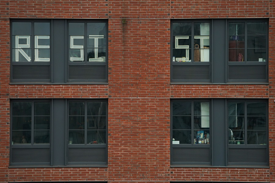 """A message to """"Resist"""" is seen in the windows of an apartment building in the Williamsburg section of Brooklyn on 25 March 2020 in New York. (Bryan R. Smith/AFP)"""
