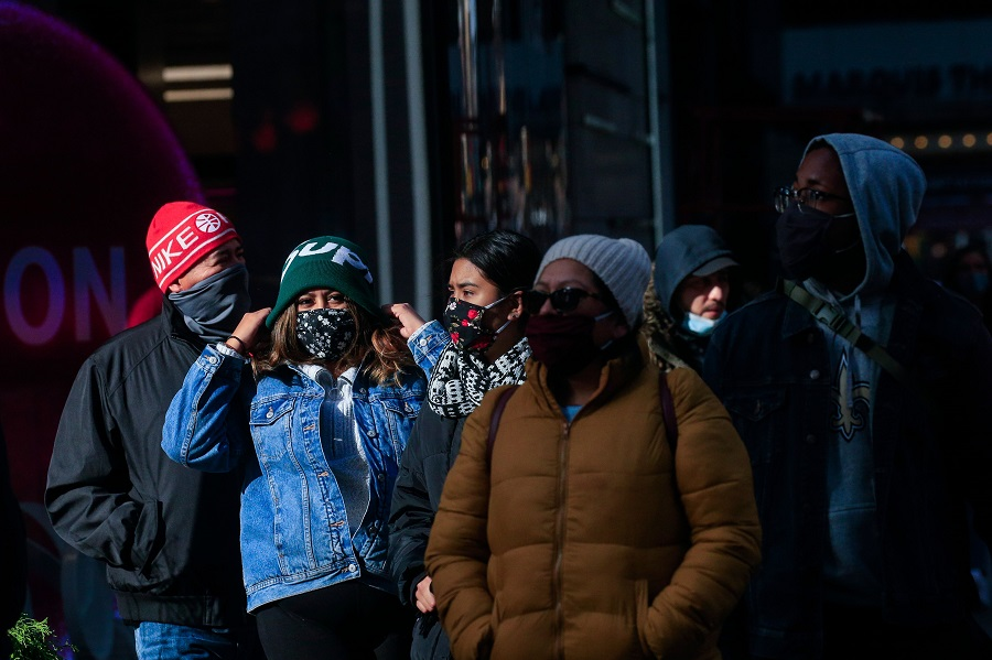 People wear face masks as they walk in Times Square in New York on 10 December 2020. (Kena Betancur/AFP)
