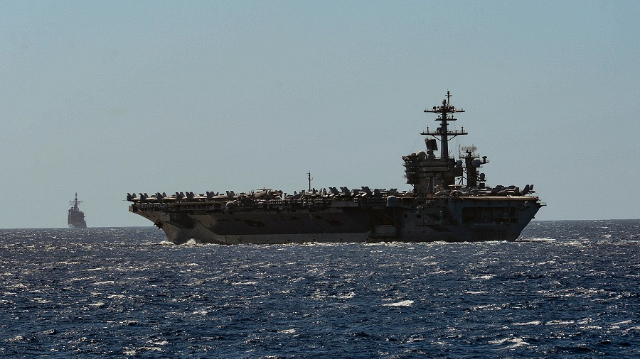 This US Navy handout photo obtained on 1 April 2020 shows the aircraft carrier USS Theodore Roosevelt and the Ticonderoga-class guided-missile cruiser USS Bunker Hill as they transit the Philippine Sea on 29 February 2020. (Sean Lynch/US Navy/Handout/AFP)