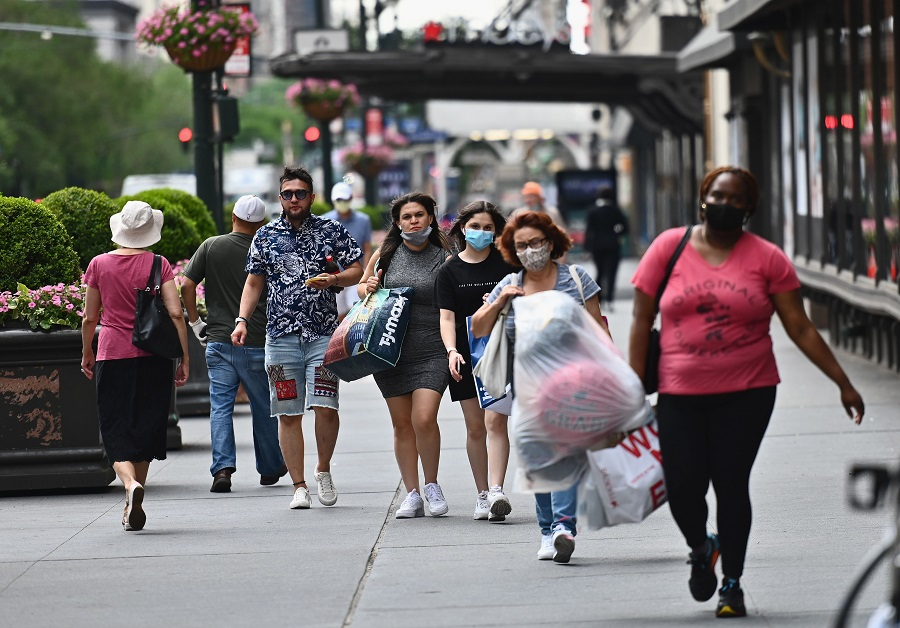 People carry shopping bags as they walk near Herald Square on 25 June 2020 in New York City. (Angela Weiss/AFP)