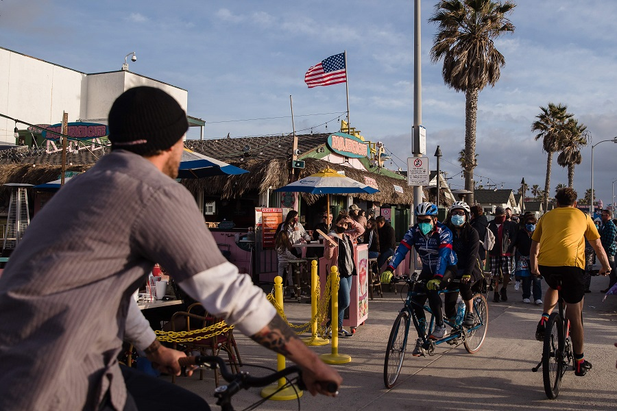 Crowds of people bike and walk the boardwalk in Pacific Beach in San Diego, California, US, on 13 February 2021. (Ariana Drehsler/AFP)