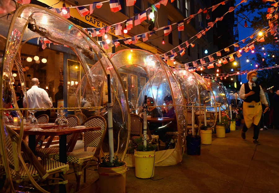 People dine in plastic tents for social distancing at a restaurant in Manhattan on 15 October 2020 in New York City, amid the coronavirus pandemic. (Angela Weiss/AFP)