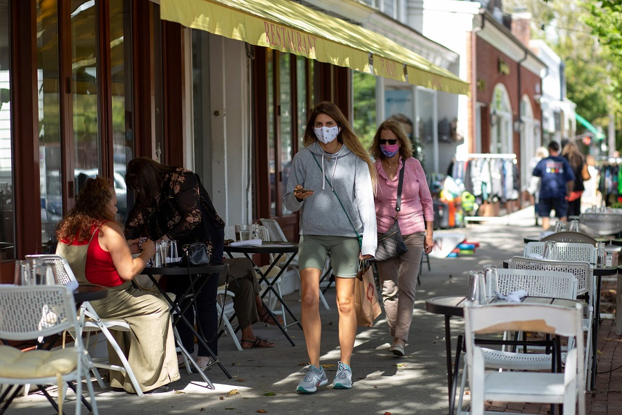 People wearing face masks walk by Main Street on 30 September 2020 in Southampton, New York. (Kena Betancur/AFP)