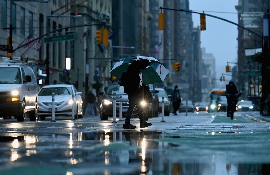 A person holding an umbrella crosses a street after heavy rainfall on 30 November 2020 in New York City. (Angela Weiss/AFP)