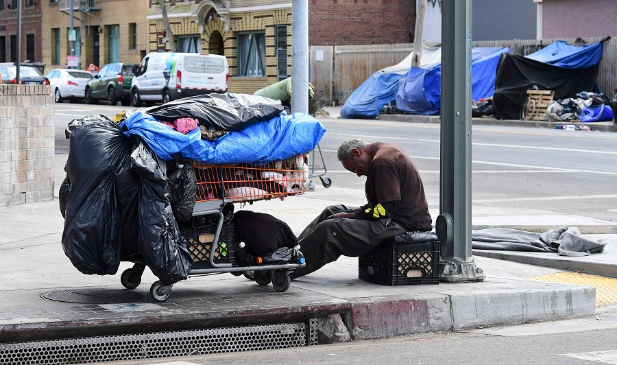 A homeless man sits beside his belongings on the streets in the Skid Row community of Los Angeles, California on 26 April 2021. (Frederic J. Brown/AFP)