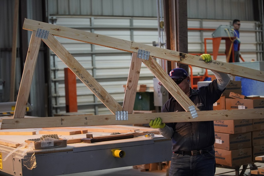 A worker carries a finished truss for a home at Wasatch Truss on 12 May 2021 in Spanish Fork, Utah, US. (George Frey/Getty Images/AFP)