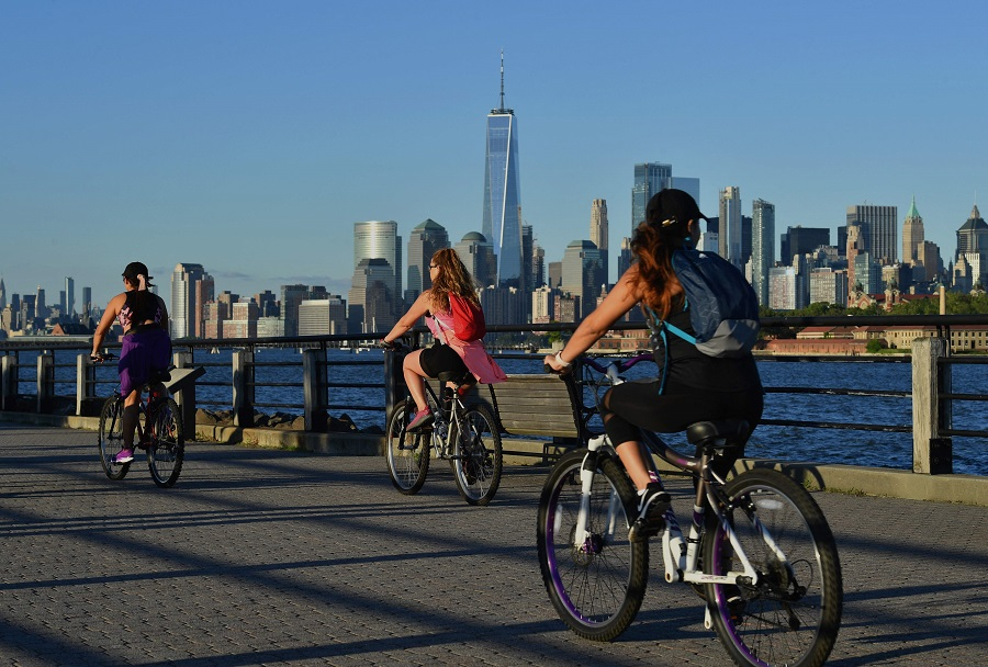 People ride their bikes along the waterfront at Liberty State Park on 24 June 2021 in Jersey City, New Jersey, US. (Angela Weiss/AFP)