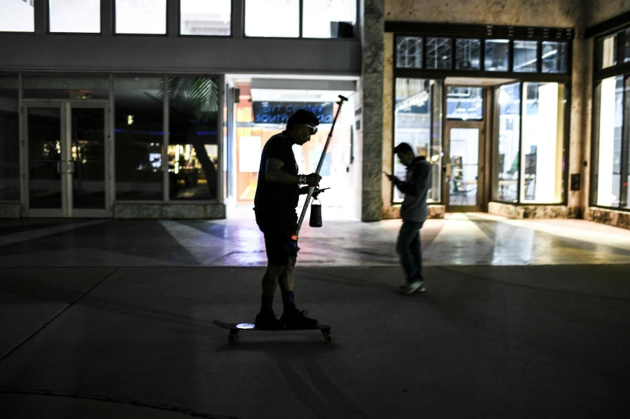 A man looks at his phone as he skateboards at a shopping district in Miami Beach, Florida, US, on 3 February 2021. (Chandan Khanna/AFP)