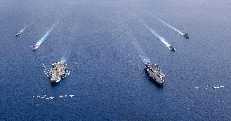This US Navy photo released on 7 July 2020 shows aircraft from Carrier Air Wings (CVW) 5 and 17 as they fly in formation over the Nimitz Carrier Strike Force, the aircraft carriers USS Nimitz (CVN 68) (right), and USS Ronald Reagan (CVN 76) as their carrier strike groups are conducting dual carrier operations in the Indo-Pacific as the Nimitz Carrier Strike Force on 6 July 2020. (Keenan Daniels/US Navy/AFP)