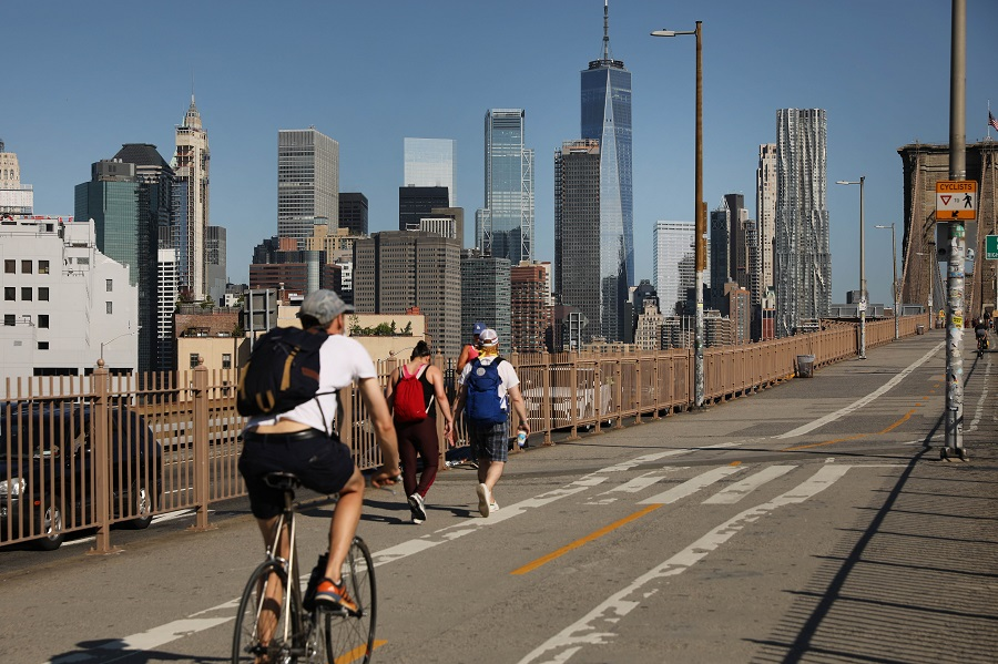 People ride their bikes across the Brooklyn Bridge as Manhattan enters Phase 2 of re-opening following restrictions imposed to curb the coronavirus pandemic on 22 June 2020 in New York City. (Spencer Platt/Getty Images/AFP)