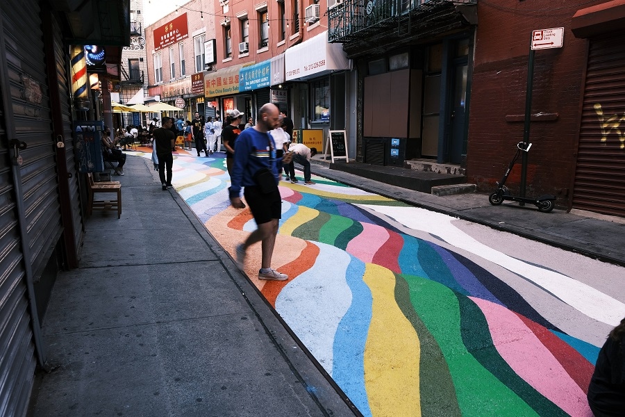People pose for photos on the historic Doyers Street in Chinatown that has been painted over by Chilean-born street artist Dasic Fernandez, 24 June 2021 in New York City, US. (Spencer Platt/Getty Images/AFP)