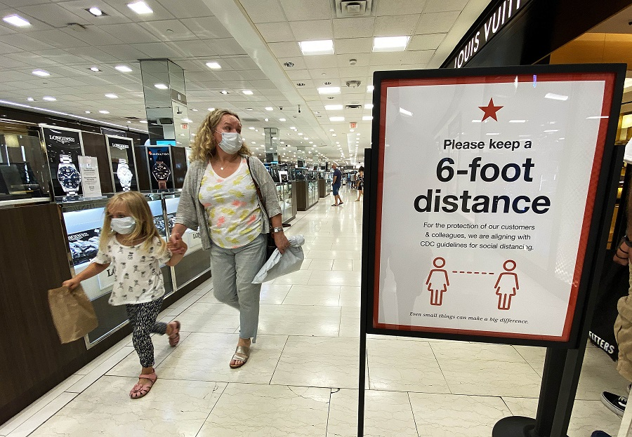Customers walk past a sign that encourages people to keep a six foot distance from each other at Roosevelt Field Mall which reopened on 10 July 2020 in Garden City, New York. ( Al Bello/Getty Images/AFP)
